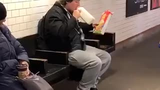 Guy drinks milk and pours cereal into his mouth in subway station