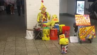 Man in yellow outfit plays drums in subway station