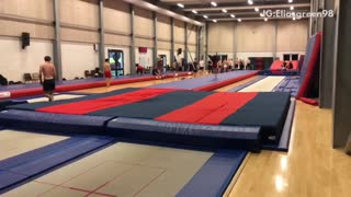 Gymnast does flips, lands on head and shoulder, bounces onto safety pad