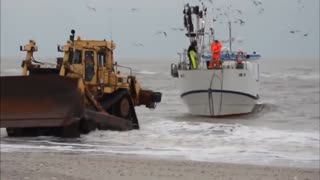 The bulldozer pulls the ship ashore - Video