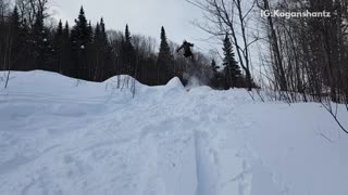 Skier does a jump off ramp and lands face first,