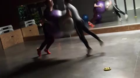Two guys run at each other with exercise ball, faces smash into each other