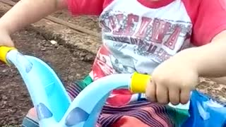 Little boy in a blue toy motorcycle falls over
