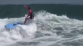 Guy in pink black wet suit surfboard slapping wave - Video