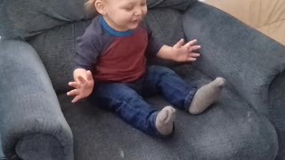Excited toddler rocks in grown up chair