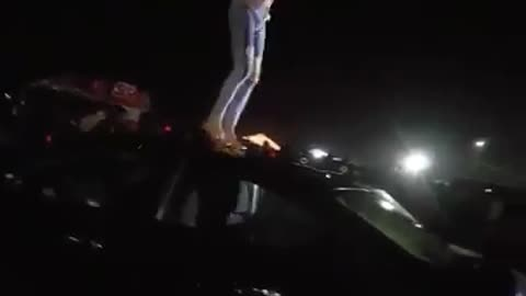 Shirtless ripped jeans guy dancing on top of black car slips face plant