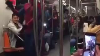 Chubby spiderman on subway train dances spanish music