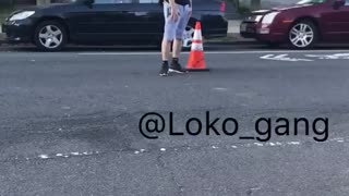Guy in black shirt puts orange cone on street