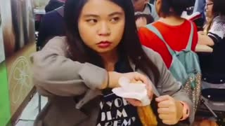 Music green jacket woman at restaurant table pulls food on stick out of jacket - Video