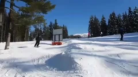 Guy in all black tries to do ski jump spin and front of ski clips floor and he fails