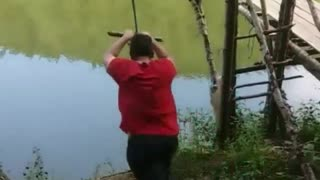 Red shirt rope swing guy falls into water