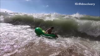 Slowmo green float guy gets destroyed by ocean wave - Video