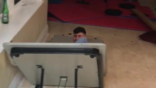 Guy blue jeans red shirt jumps and breaks white folding table - Video