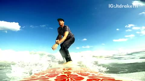 Guy in button down shirt and jeans surfs on a red surfboard