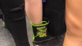 This a grown woman wearing ninja turtle rain boots