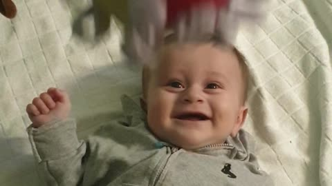 Baby boy adorably cracks up every time toy ball is dropped on him