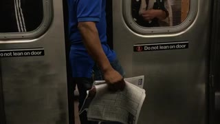 Man in a blue shirt standing between train doors - Video