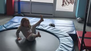Little girl shoots basketball into hoop while on trampoline and falls back