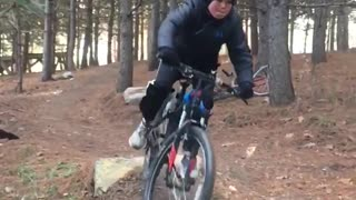 Kid on red black bike falls on handle bars while riding