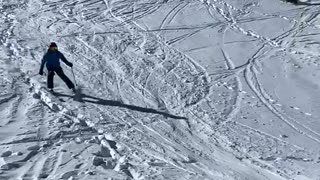 Skier skis down slope, flies off a ramp and falls