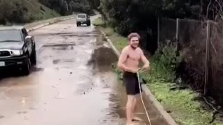Shirtless guy in black shorts wakeboarding on flooded streets falls immediately - Video