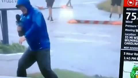 Weather Channel reporter braces against wind as others just stroll by