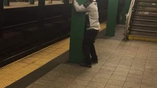 Guy hat backwards face between green pillar subway - Video