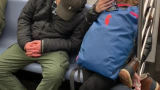 Man falls asleep on woman's shoulder on subway train, woman makes funny face