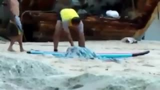 Guy yellow shirt kicking sand out of the way at beach