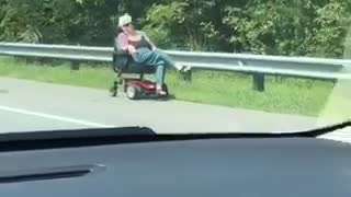 Woman on red scooter drives down highway  - Video
