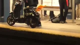 Man walking through train subway station with moped scooter bike