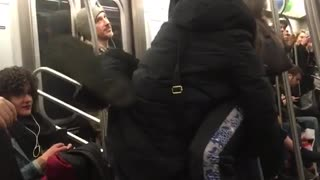 A couple hanging from subway rails man wraps legs on woman - Video