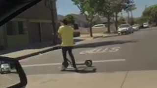 Kid yellow shirt using bird electric scooter while riding skateboard