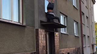 Guy does handstand on awning in front of apartment  - Video