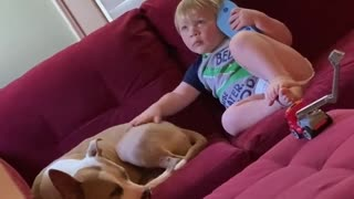 Kid uses flip flop as a phone while petting his doggy friend