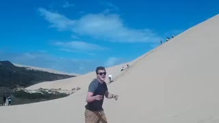 Sunglasses guy surfs down sand dune and faceplants - Video