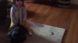 Kid watches sesame street and sits on black dog - Video