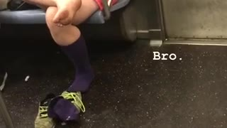 A woman in pink with her bare foot out on subway train - Video