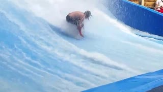 Long haired man falls off artificial surf machine - Video