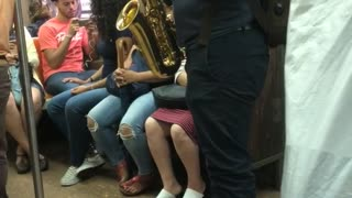 Guy green backpack playing saxophone on subway train