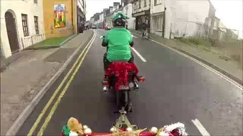 Santa arrives on motorcycle towed sleigh