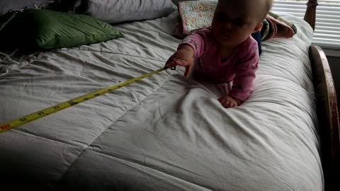 Baby laughs hysterically at measuring tape