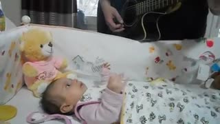 Beba cautivada por su papá mientras toca la guitarra - Video