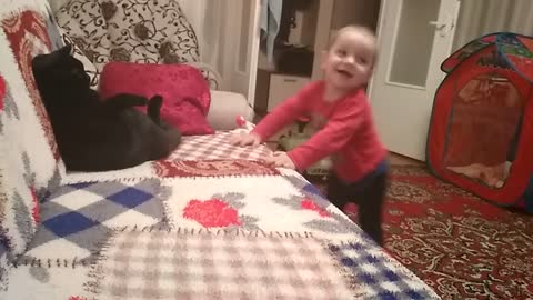 Cat plays with baby
