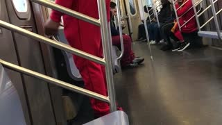Man in red sweats dances by subway doors
