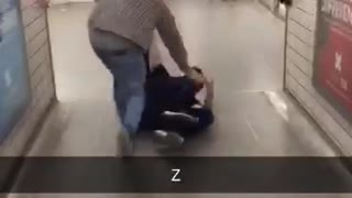 Two guys dragging another one through a subway station