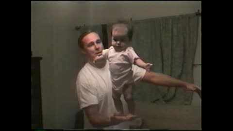 Father Balances Standing Baby Perfectly In One Hand