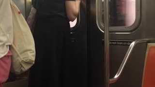 Guy green shirt pony tail staring at subway door - Video