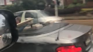A man in grey car top down with surf board