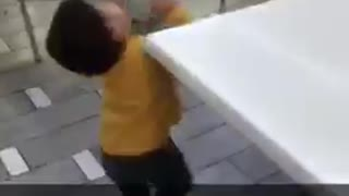 Tiny boy in yellow shirt hits head on table - Video